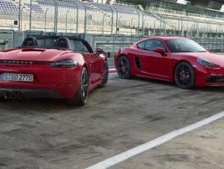 Zwei rote Porsche 718 Boxster und Cayman stehen in der Boxengasse einer Rennstrecke.