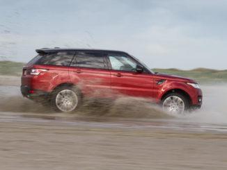 Ein roter Range Rover Sport fährt 2018 durch Schlamm.