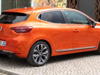 Ein orangener Renault Clio V steht 2019 vor einer Graffitiwand.