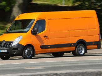 Ein orangener Renault Master fährt 2014 an einer Parkanlage entlang.