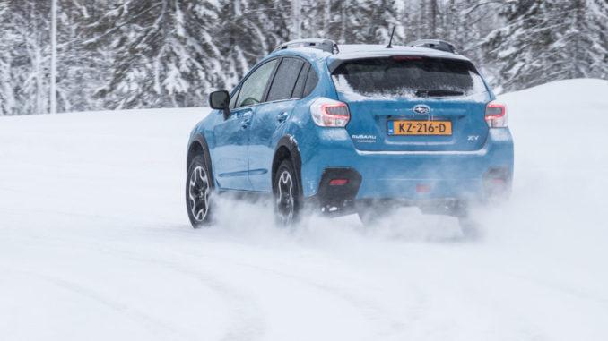 Ein hellblauer Subaru XV fährt 2016 durch eine Winterlandschaft.