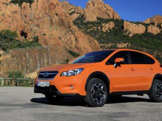 Ein orangener Subaru XV steht 2012 vor ockerfarbenen Felsen.