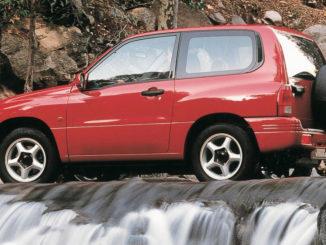 Ein roter Suzuki Grand Vitara Limousine 2.0 Liter fährt 1998 über einen Wasserfall.