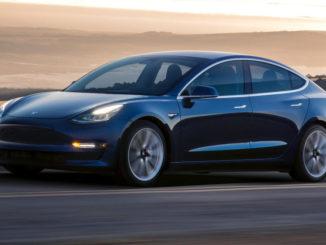 Ein blauer Tesla Model 3 fährt 2018 durch eine Wüstenlandschaft.