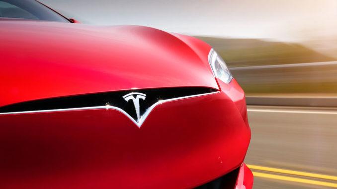 Ein roter Tesla Model S fährt 2017 auf einer US-amerikanischen Landstraße.