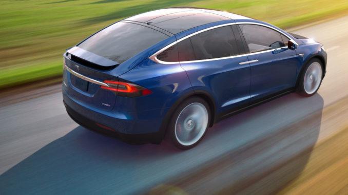 Ein blauer Tesla Model X fährt auf einer Landstraße.
