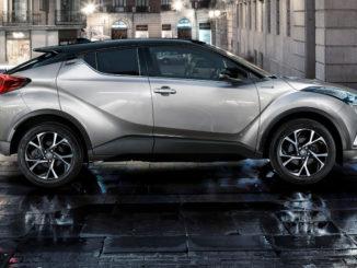 Ein silberner Toyota C-HR steht auf einem regennassen Stadtplatz.