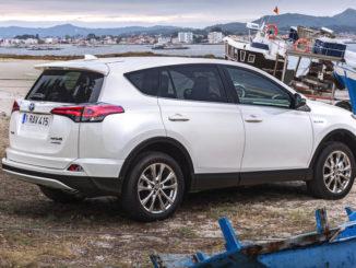 Ein weißer Toyota RAV4 Hybrid steht 2016an einem kleinen Mittelmeerhafen zwischen Schiffen.