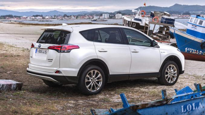 Ein weißer Toyota RAV4 Hybrid steht 2016 an einem kleinen Mittelmeerhafen zwischen Schiffen.