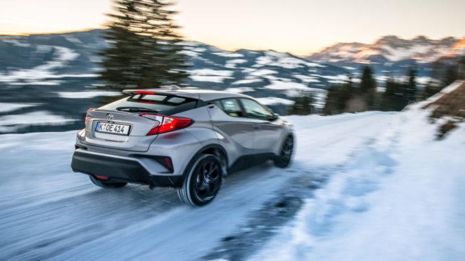Ein silberner Toyota C-HR bremst auf schneeglatter Landstraße in den Alpen.