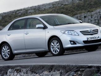 Ein silberner Toyota Corolla steht 2008 vor einer Steinmauer.
