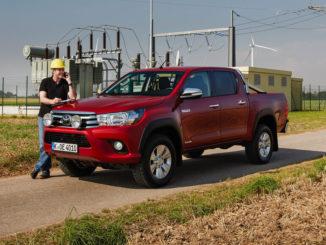 Ein roter Toyota Hilux steht 2018 vor einem Schaltwerk.