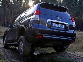Ein dunkelblauer Toyota Landcruiser 150 fährt 2011 durch unwegsames Gelände im Wald.