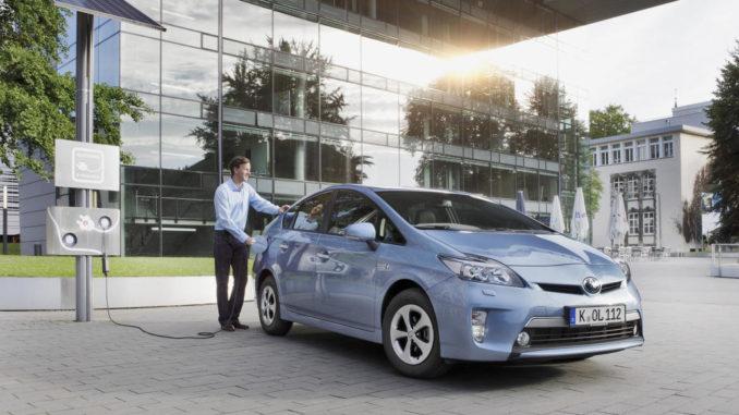 Ein blauer Toyota Prius PHV steht 2014 an einer Ladesäule.
