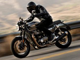 Ein schwarz gekleideter Mann fährt auf einer schwarzen Triumph Speed Twin des Modelljahres 2019 auf einer durch einer Leitplanke begrenzten Landstraße vor einem Bergpanorama.