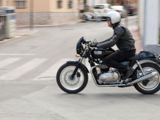 Ein Mann fährt auf einer schwarzen triumph_thruxtondurch die Straßen einer Stadt.