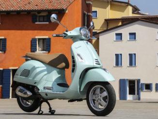 Eine türkise Vespa GTS 300 steht 2019 auf einem italienischen Dorfplatz.