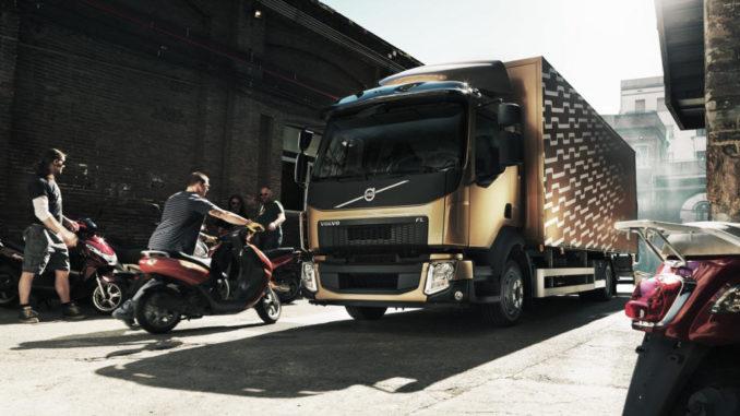 Ein kupferfarbender Volvo FL wird mit Rollern beladen