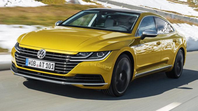Ein goldener VW Arteon fährt durch eine verschneite Landschaft.