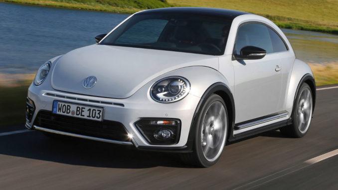 Ein weißer VW Beetle fährt 2016 ein Seeufer entlang.