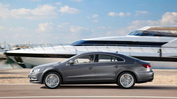 EIn silbergruaer VW CC fährt in einem Hafen an einer Yacht vorbei. CC 3.6 V6 4MOTION - Kraftstoffverbrauch in l/100 km: kombiniert 9,3; CO2-Emission kombiniert in g/km: 215