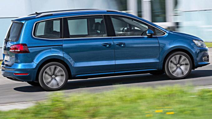 Ein blauer VW Sharan 2.0 TDI fährt 2015 an einem weißen Gebäude vorbei.