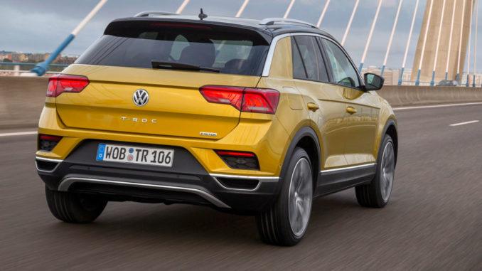 Ein goldener VW T-Roc fährt über eine Brücke.