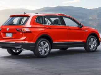 Ein roter VW Tiguan steht in den USA vor einem Bergsee.