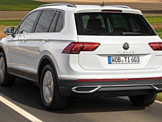 Ein weißer VW Tiguan eHybrid fährt 2020 auf einer Landstraße.