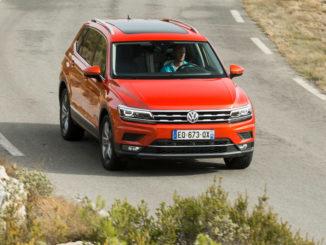 Ein roter VW Tiguan Allspace fährt auf einer mediterranen Landstraße.