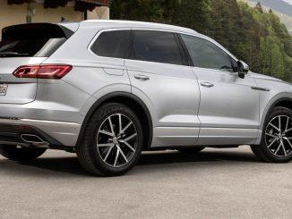 Ein silberner VW Touareg Elegance steht 2018 vor einem Haus in den Alpen.