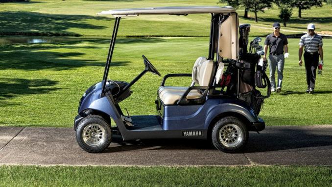Ein blaues Golf Cart von Yamaha, modell Drive2, steht auf einem Weg am Rande eines Platzes.