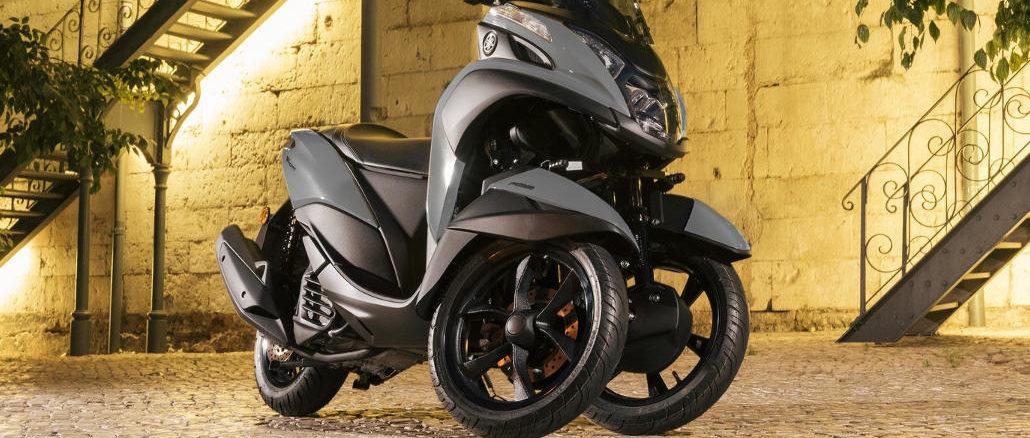 Eine schwarze Yamaha Tricity Modelljahr 2018 steht in einem Hinterhof.